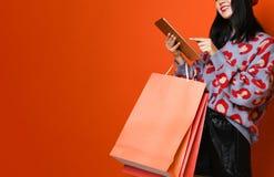 Kvinna som rymmer den shoppa p?sen och anv?nder minnestavlan f?r att shoppa som ?r online- som shoppar begrepp arkivbilder