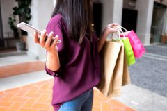 Kvinna som rymmer den shoppa påsen och använder smartphonen för att shoppa som är online- som shoppar begrepp royaltyfria bilder