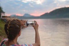Kvinna som rymmer den smarta telefonen som fotograferar Mekong River på Luang Prabang Laos, dramatisk himmel för solnedgång, berö royaltyfri fotografi