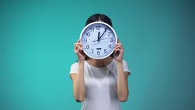 Kvinna som rymmer den stora klockan för hennes framsida, tidledning och rutin, stopptid arkivfilmer
