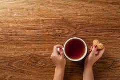 Kvinna som rymmer den varma kopp te med kakor Arkivfoto