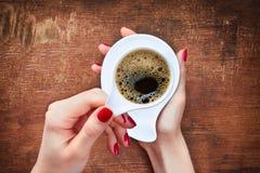 Kvinna som rymmer den varma koppen kaffe Arkivbilder