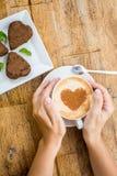 Kvinna som rymmer den varma koppen kaffe, med hjärtaform och choklad Arkivbilder