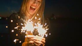 Kvinna som rymmer det brännande tomteblosset Gladlynt ung kvinna som rymmer två tomtebloss i helgdagsafton för nytt år s för hand arkivfilmer