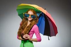 Kvinna som rymmer det färgglade paraplyet Arkivfoto