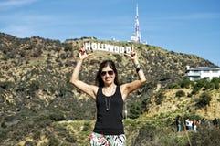 Kvinna som rymmer det Hollywood tecknet arkivfoto
