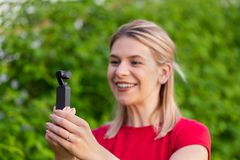 Kvinna som rymmer DJI Osmo Camera royaltyfri foto