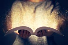 Kvinna som rymmer en öppen bok som brister med ljus royaltyfri fotografi