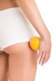 Kvinna som rymmer en apelsin mot hennes lår royaltyfri bild