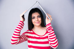 Kvinna som rymmer en bärbar dator ovanför hennes huvud som ett tak Fotografering för Bildbyråer