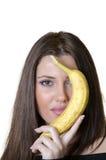 Kvinna som rymmer en banan som döljer hennes halva framsida Arkivfoton