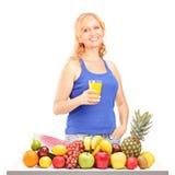 Kvinna som rymmer en drink främre av stapel av frukt Royaltyfria Foton