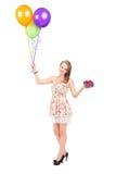 Kvinna som rymmer en gåva och en grupp av ballonger Fotografering för Bildbyråer