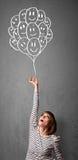Kvinna som rymmer en grupp av att le ballonger Arkivfoton