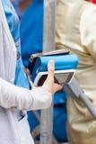 Kvinna som rymmer en handväska och mobiltelefon två i hennes hand Royaltyfri Foto