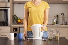 Kvinna som rymmer en kokkärl som gör te arkivfoton