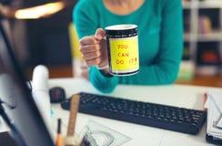 Kvinna som rymmer en kopp kaffe med ett motivational meddelande Arkivfoto