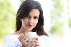 Kvinna som rymmer en kopp kaffe som ser kameran royaltyfri foto