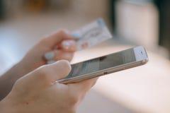 Kvinna som rymmer en kreditkort och använder mobiltelefonen för online-shopping Royaltyfri Fotografi