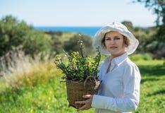 Kvinna som rymmer en kruka med växten Royaltyfri Foto