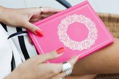 Kvinna som rymmer en liten rosa färgbok arkivbild