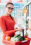 Kvinna som rymmer en livsmedelsbutikkorg royaltyfri foto