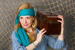 Kvinna som rymmer en piratkopiera med en bröstkorg Royaltyfri Bild