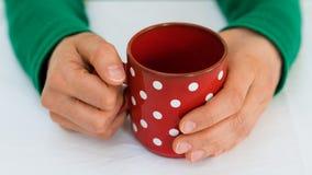 Kvinna som rymmer en röd kaffekopp med vita prickar på en vit tabelltorkduk arkivfoton