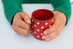 Kvinna som rymmer en r?d kaffekopp med vita prickar p? en vit tabelltorkduk royaltyfri bild