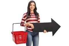 Kvinna som rymmer en shoppingkorg och pil Arkivfoton