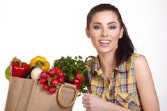 Kvinna som rymmer en shoppingpåse full av ny mat Royaltyfri Fotografi