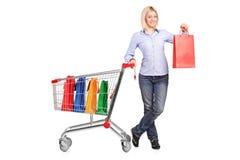 Kvinna som rymmer en shoppingpåse och skjuter en shoppingvagn Fotografering för Bildbyråer