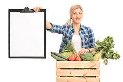 Kvinna som rymmer en skrivplatta som säljer grönsaker Arkivbilder