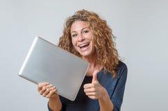 Kvinna som rymmer en splitterny bärbar dator Royaltyfria Bilder