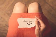 Kvinna som rymmer en tacka dig för att notera i hennes hand arkivfoton