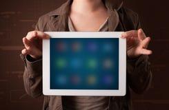 Kvinna som rymmer en vit minnestavla med oskarpa apps royaltyfri bild