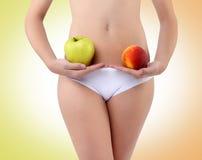 Kvinna som rymmer ett äpple och en persika med hans händer nära buken Royaltyfria Bilder