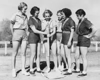 Kvinna som rymmer ett baseballslagträ och ger utbildning till andra kvinnor (alla visade personer inte är längre uppehälle, och i royaltyfri foto