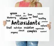 Kvinna som rymmer ett bräde med Antioxidantsbegrepp royaltyfri bild