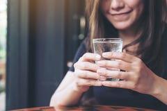 Kvinna som rymmer ett exponeringsglas av kallt vatten för att dricka fotografering för bildbyråer
