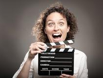 Kvinna som rymmer ett filmclapperbräde Arkivbild