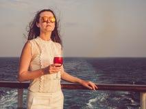 Kvinna som rymmer ett härligt exponeringsglas av vin royaltyfri bild