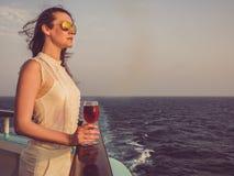Kvinna som rymmer ett h?rligt exponeringsglas av vin royaltyfri fotografi