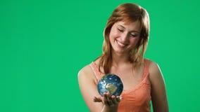 Kvinna som rymmer ett jordklot i hennes hand lager videofilmer