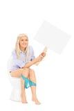 Kvinna som rymmer ett tomt tecken placerat på en toalett Royaltyfri Foto