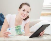 Kvinna som rymmer 100 euro och minnestavlaapparaten Arkivfoton