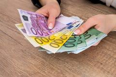 Kvinna som rymmer 100 200 500 euroräkningar Royaltyfri Bild