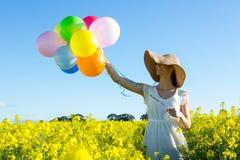 Kvinna som rymmer färgrika ballonger i senapsgult fält royaltyfri foto