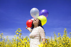Kvinna som rymmer färgrika ballonger i senapsgult fält på en solig dag Arkivbild