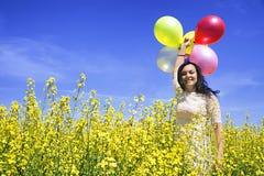 Kvinna som rymmer färgrika ballonger i senapsgult fält på en solig dag royaltyfri fotografi